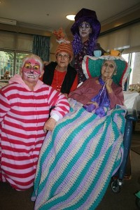 Fun: volunteer Janet Lester enjoyed her role as Cheshire Cat at the Koorooman House madhatters' tea party. Marlene Hanks is standing while resident Dorothy Boscombe kept her amazing hat on her head with the encouragement of her daughter Pam Charman, wearing her own over-sized tea cosy.