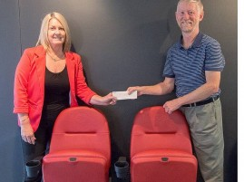 Goal reached: a happy moment for Lyric Theatre vice president Ross Garner as he hands over the cheque from Lyric Theatre to a Camatic representative, finalising the purchase of the new seats.