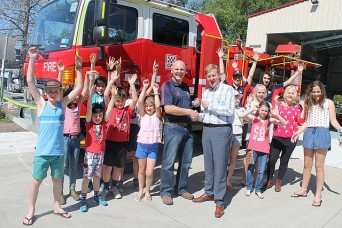 Ready to go: Deputy Premier, Peter Ryan hands over the keys of the new $275,000 Hino  fire truck to CFA Koonwarra captain, Peter Hanily to the great delight of a large gathering of the community's youngsters.