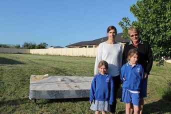 Just garbage: Lisa, Isla and Sienna Burge and Heather Poletti with the piece of rubbish that was discarded on their Leongatha property. They are now stuck with the garbage and are faced with a cost of $40 to dispose of it correctly.