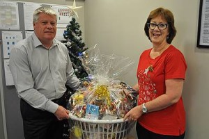 Christmas bonus: winner of Gippsland Southern Health Service's raffle, Sue Wright, receives her hamper from CEO Mark Johnson.
